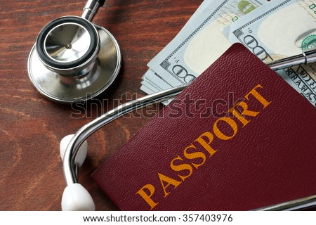 Medical tourism concept. Stethoscope with passport and dollar bills.  - stock photo
