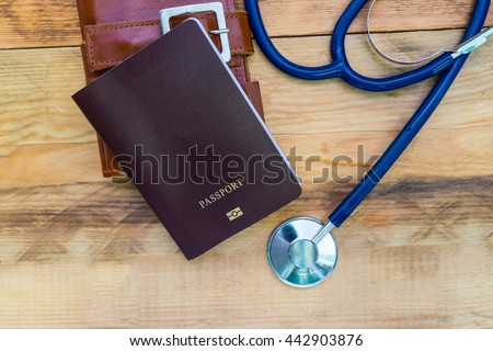 Medical tourism concept. Stethoscope with passport on wooden table. - stock photo