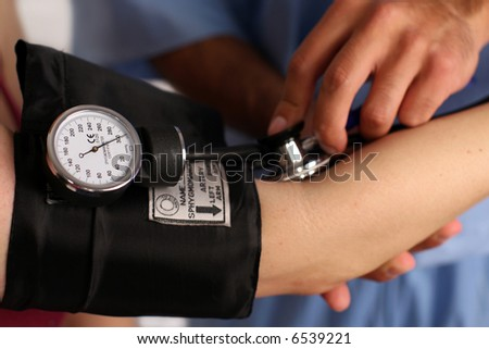 Medical worker checking blood pressure - stock photo