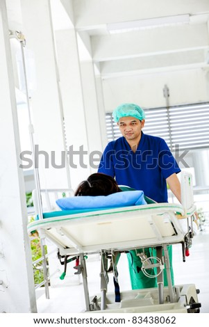 medical worker moving patient on hospital trolley to operating room - stock photo