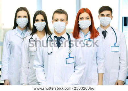 Medical workers in medical masks in conference room - stock photo