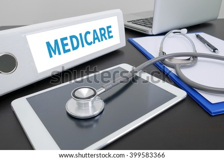 MEDICARE folder on Desktop on table. ipad - stock photo