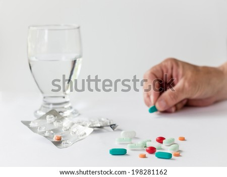 medication and pills with a glass of water and a hand holding a pill isolated on white background. - stock photo