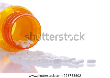 medication bottle on side with pills spilling out onto a reflective surface. Reflection of medication tablets on the table.