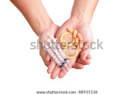 medication , syringe needle and condom holding by hands - stock photo