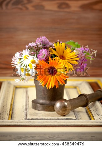 medicinal herbs  and flowers in a mortar on a wooden table
