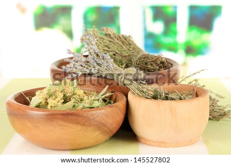 Medicinal Herbs in wooden bowls on striped tablecloth on table on window background - stock photo