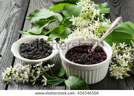 Medicinal plant - bird cherry (Prunus padus). Flowering branches, dried berries and jam on a white wooden background. Selective focus  - stock photo