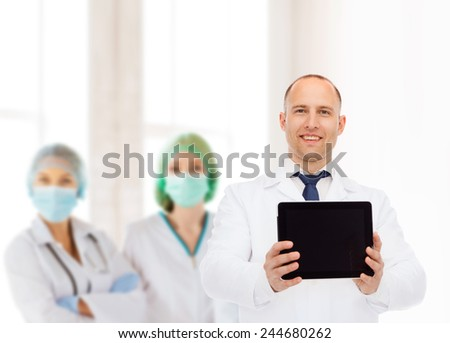 medicine, advertisement and teamwork concept - smiling male doctor showing tablet pc computer screen over group of medics - stock photo