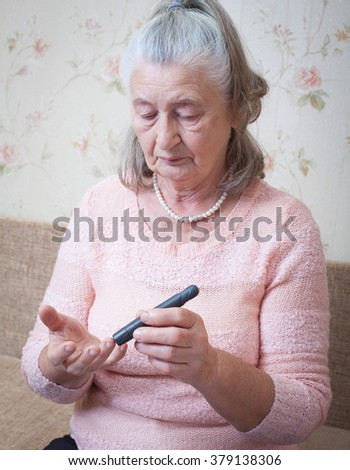 Medicine, age, diabetes, health care and people concept - senior woman with glucometer checking blood sugar level at home closeup