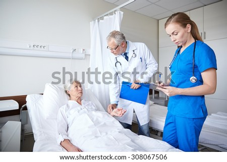 medicine, age, health care and people concept - doctor and nurse with clipboards visiting senior patient woman and checking her pulse at hospital ward - stock photo
