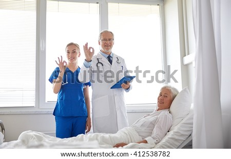 medicine, age, health care and people concept - doctor and nurse with tablet pc computer visiting senior patient woman and showing ok sign at hospital ward - stock photo