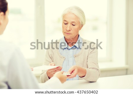medicine, age, health care and people concept - doctor giving prescription and pills to senior woman at hospital - stock photo