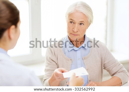 medicine, age, health care and people concept - doctor giving prescription to senior woman at hospital - stock photo
