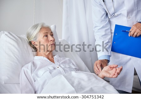 medicine, age, health care and people concept - doctor with clipboard visiting senior patient woman and checking her pulse at hospital ward - stock photo