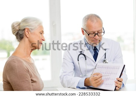 medicine, age, health care and people concept - senior woman and doctor meeting in medical office - stock photo