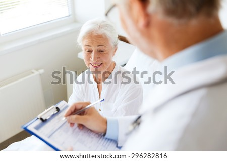 medicine, age, health care and people concept - senior woman and doctor writing to clipboard at hospital ward - stock photo