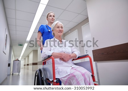 medicine, age, support, health care and people concept - nurse taking senior woman patient in wheelchair at hospital corridor - stock photo