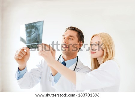 medicine and healthcare concept - smiling male doctor or dentist with nurse looking at x-ray in hospital - stock photo