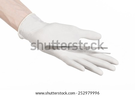 Medicine and Surgery theme: doctor's hand in a white glove holding tweezers isolated on white background - stock photo