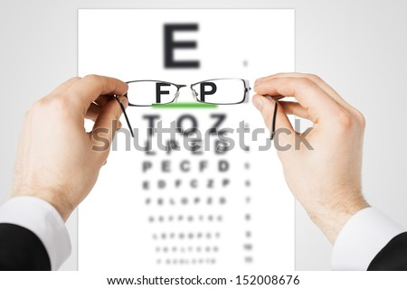 medicine and vision concept - man looking at eye chart through eyeglasses - stock photo