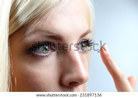 Medicine and vision concept - young woman with contact lens, close up - stock photo