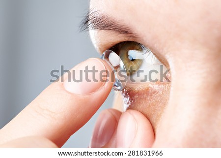Medicine and vision - young woman with contact lens - stock photo