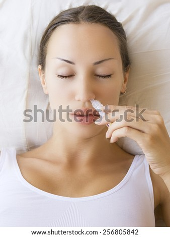 Medicine ayurvedic spray nasal. Sick young woman using nasal spray and laying on sofa