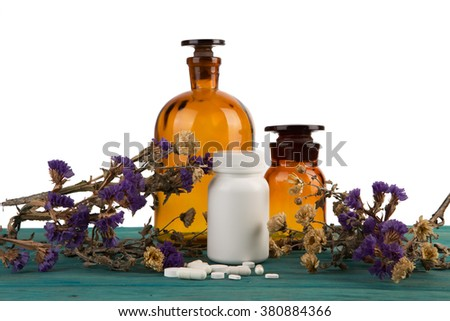 medicine bottles on wooden table isolated on blue with flower and pils - stock photo