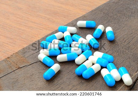 medicine capsule pill on wood background - stock photo