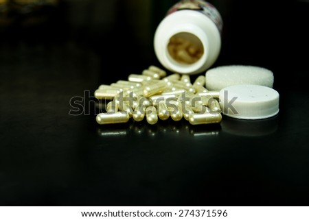 medicine capsule spilling out of a bottle. - stock photo
