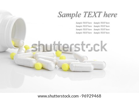 medicine capsules scattered on a white background with room for text - stock photo