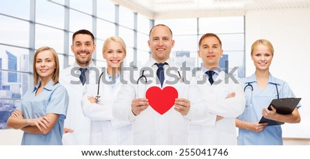medicine, cardiology, healthcare and people concept - happy young doctors cardiologists with red heart over clinic background - stock photo