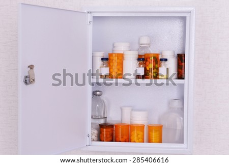 Medicine chest with bottles of pills hanging on wallpaper background