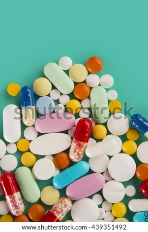 Medicine colorful vitamins, pills and tablets on green background