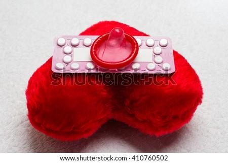 Medicine contraception love and birth control. Oral contraceptive pills condom on red heart shaped little pillow - stock photo
