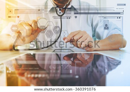 Medicine doctor hand holding stethoscope with modern computer interface as medical network concept - stock photo