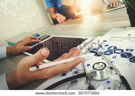 Medicine doctor hand working with modern computer and digital pro tablet with blank screen with his team on wooden desk as medical concept - stock photo