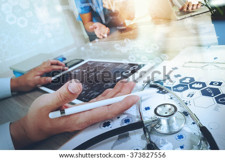 Medicine doctor hand working with modern computer and digital pro tablet with his team with digital medical diagram on wooden desk as medical concept                                - stock photo