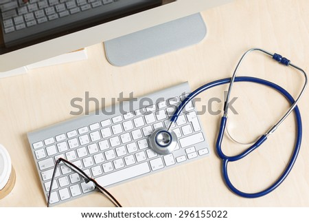 Medicine doctor's working table view from top. Monitor, keyboard, mouse and stethoscope lying on table at physician's office. Medical concept - stock photo
