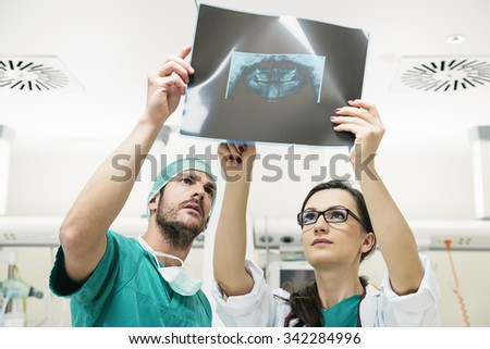 Medicine doctor showing something to her male colleague on x-ray image. Healthcare and medical concept - stock photo