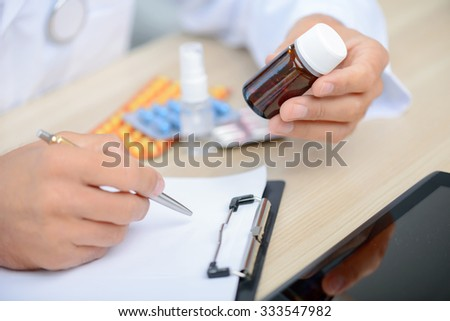 Medicine for you. Close up of professional doctor holding bottle with pills and making notes while sitting at the table