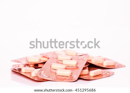Medicine green and yellow pills or capsules on white background with copy space. Drug prescription for treatment medication. Pharmaceutical medicament, cure in container for health. Antibiotic