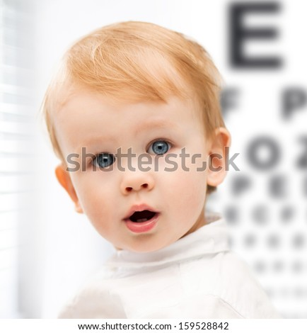 medicine, health and vision concept - adorable baby child with eyesight testing board - stock photo