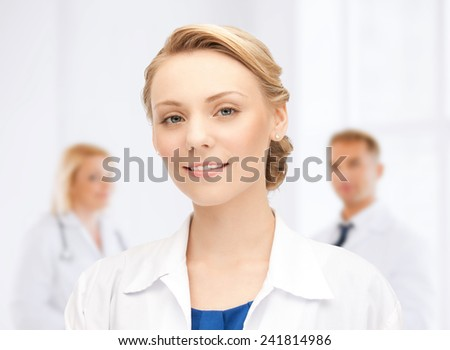 medicine, people, profession and teamwork concept - smiling young female doctor over group of medics in hospital - stock photo