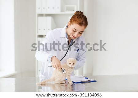 medicine, pet, animals, health care and people concept - happy veterinarian doctor with stethoscope checking scottish fold kitten up at vet clinic - stock photo