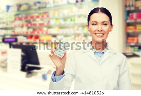 medicine, pharmacy, people, health care and pharmacology concept - happy young woman pharmacist with pills over drugstore background - stock photo
