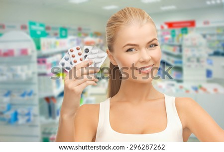 medicine, pharmacy, people, health care and pharmacology concept - happy young woman with variety of pills over drugstore background - stock photo