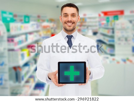 medicine, pharmacy, people, health care and pharmacology concept - smiling male doctor showing tablet pc computer with cross symbol on screen over drugstore background - stock photo