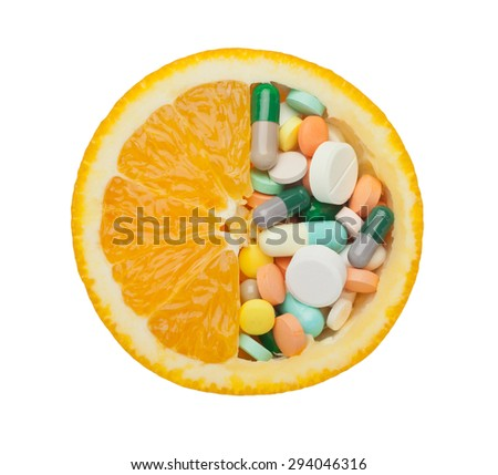 Medicine pills in an orange isolated on white background